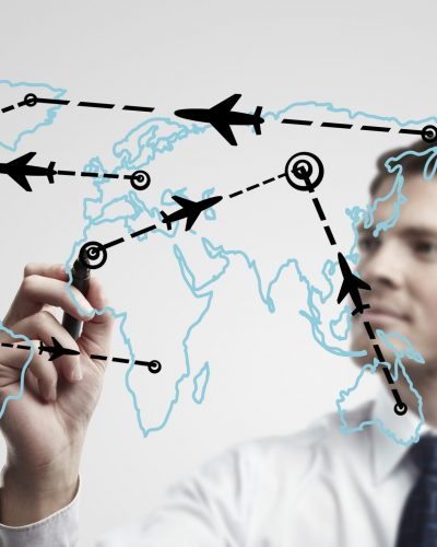 Young business man drawing an airplane routes on world map. Man drawing world map with aircraft flying on a glass window.